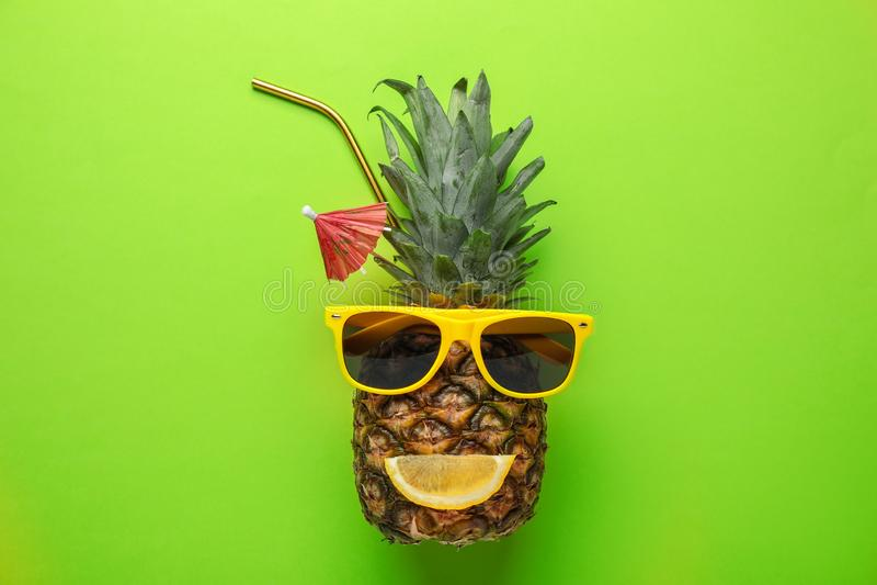 Ananas med den roliga framsidan som göras av solglasögon och citrus skiva som sommarcoctailen på färgbakgrund royaltyfri foto