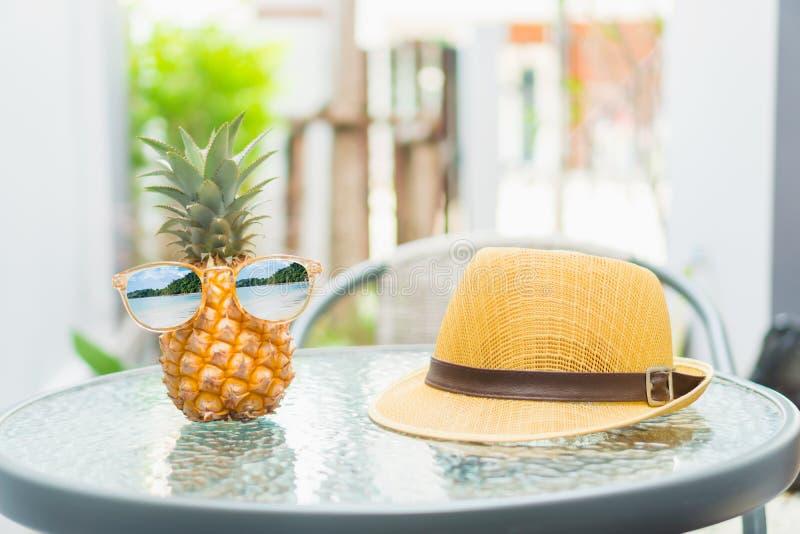 Ananas med exponeringsglas är sliten, och en hatt förläggas på tabellen sommar för snäckskal för sand för bakgrundsbegreppsram royaltyfri foto