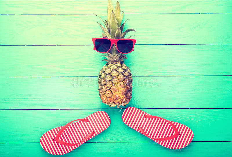 Ananas met glazen en pantoffels op blauwe houten achtergrond Exemplaar ruimte en hoogste mening stock afbeeldingen