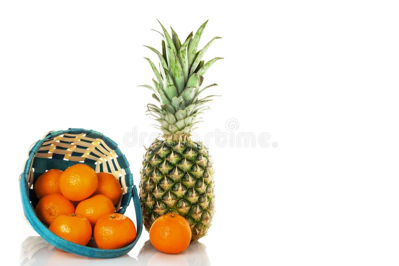 Ananas met mand en met kleine mandarijnen op een witte achtergrond isoleer stock afbeelding