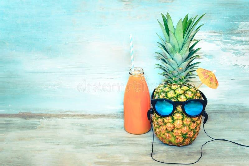 Ananas mit Sonnenbrille und Kopfhörer und eine Flasche Saft vor einem blauen hölzernen rustikalen Hintergrund Sommerferienpartei stockfoto