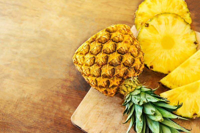 Ananas na drewnianym tekstury tle Cały i pokrojony tropikalny ananas na drewnianej tnącej desce z kopii przestrzenią Odgórny wido zdjęcie stock