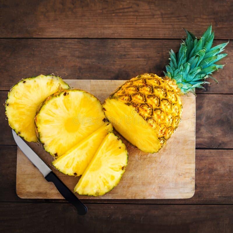 Ananas na drewnianym tekstury tle Cały i pokrojony tropikalny fotografia royalty free