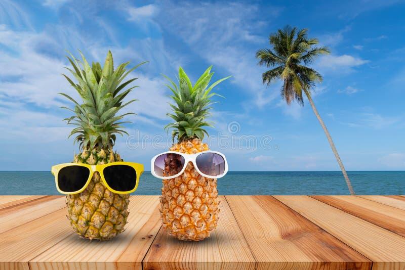 Ananas op houten lijst in een tropisch landschap, Manier hipster ananas, Heldere de zomerkleur, Tropisch fruit met zonnebril royalty-vrije stock foto's