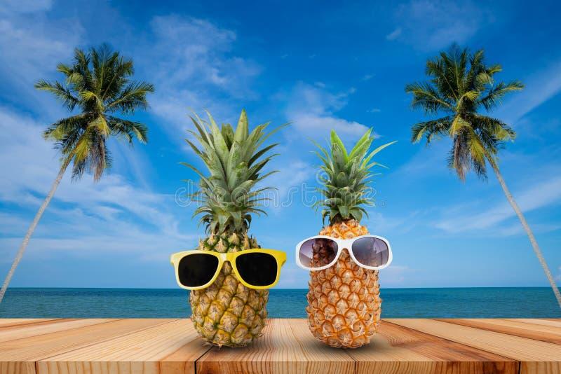 Ananas op houten lijst in een tropisch landschap, Manier hipster ananas, Heldere de zomerkleur, Tropisch fruit met zonnebril stock fotografie