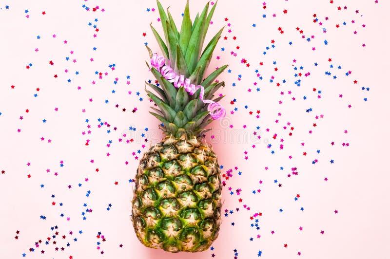 Ananas op roze pastelkleur in achtergrond met confettien en sterren Feestelijke achtergrond voor pakket royalty-vrije stock fotografie