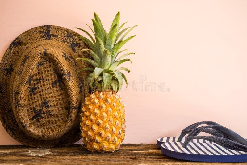 Ananas organique, bascules électroniques et chapeau de paille sur la vieille table en bois images stock