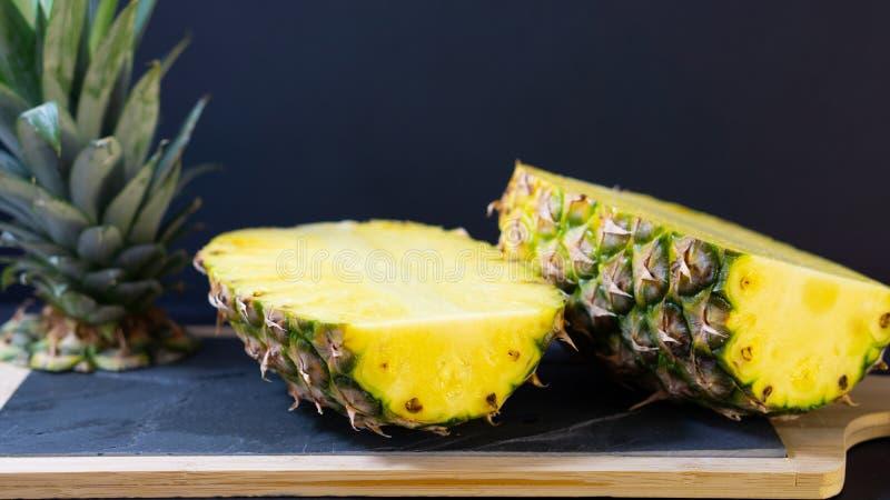 Ananas på ett stenbräde med en träram klipps i halva royaltyfri bild