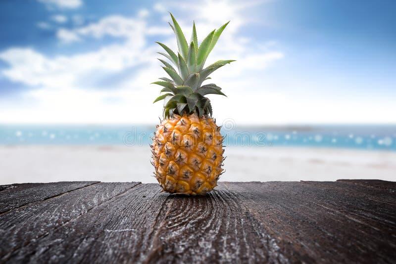 Ananas på träskrivbord- och strandsidobakgrund arkivfoton