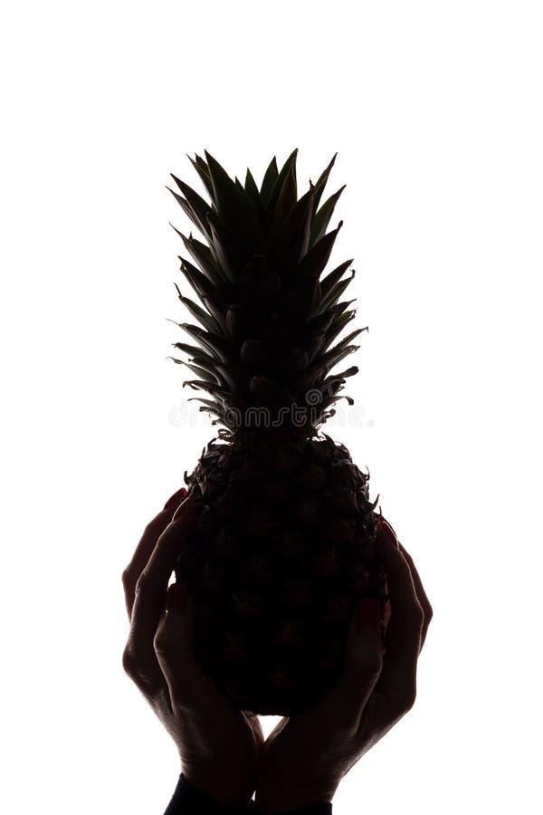 Ananas p? h?nder f?r kvinna` ett s p? vit bakgrund royaltyfria bilder