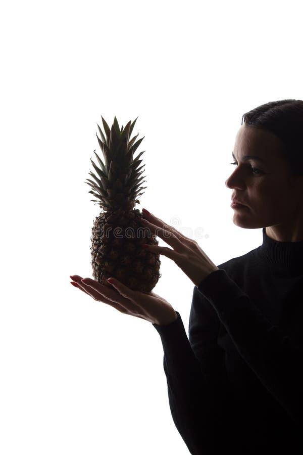 Ananas p? h?nder f?r kvinna` ett s p? vit bakgrund arkivbild