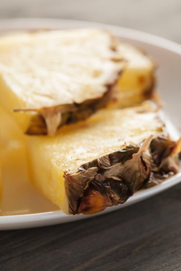 Ananas skivar stycken på en vit platta på trätabellen royaltyfri bild