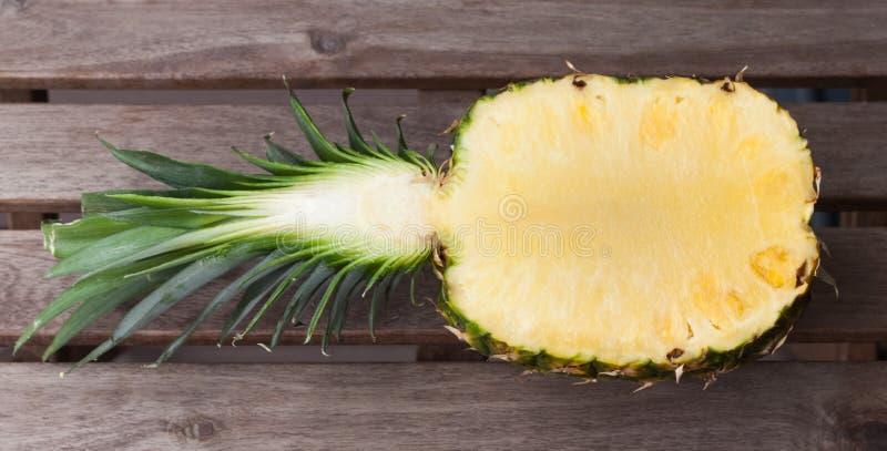 Ananas som är halv på en träbakgrund arkivfoton