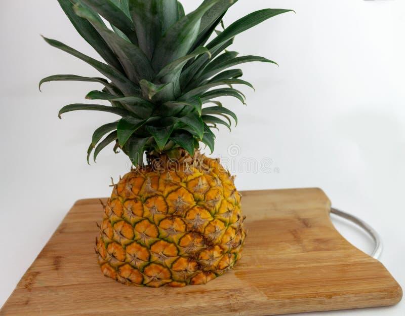 Ananas tagliato a metà su un tagliere immagine stock