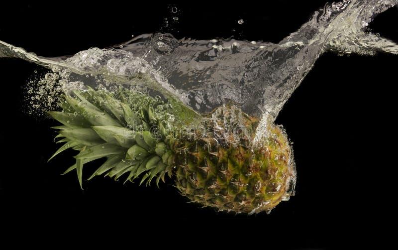 Ananas tombant sous l'eau avec la grande éclaboussure images libres de droits