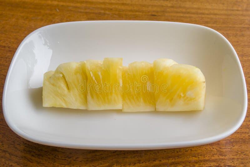 Ananas in una ciotola bianca su una tavola di legno immagine stock
