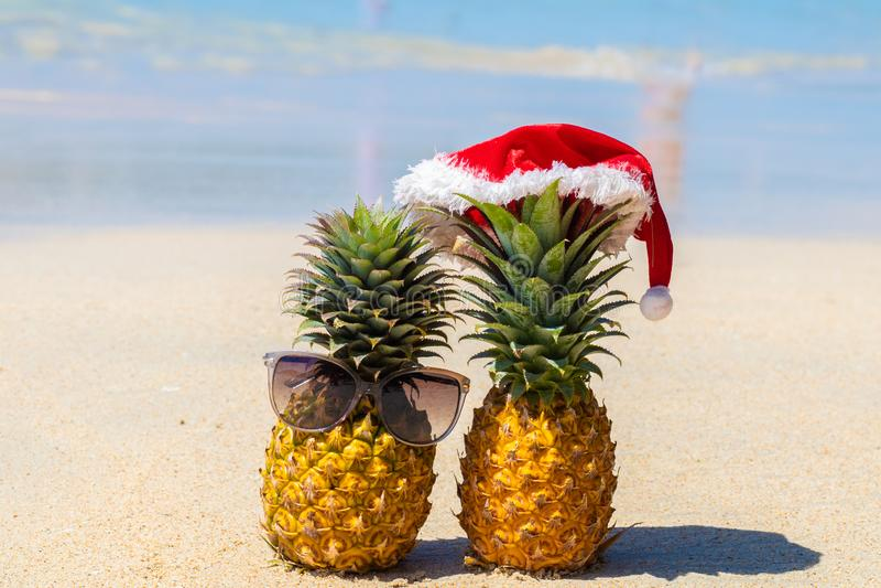 Ananas w szkłach i Bożenarodzeniowym kapeluszu na białym piasku przegapia błękitnego morze obrazy royalty free