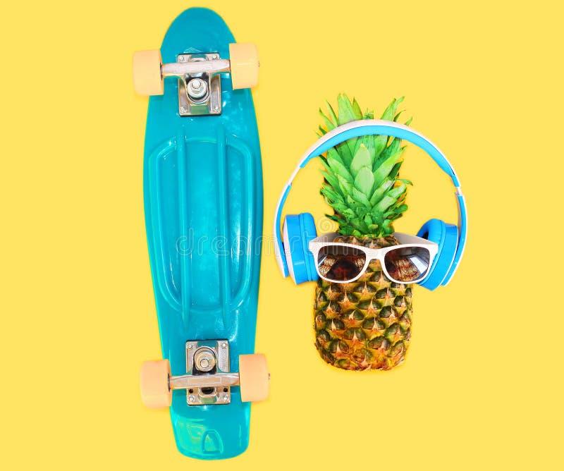 Ananas z hełmofonów okularami przeciwsłonecznymi i deskorolka nad kolorowym kolorem żółtym zdjęcie stock