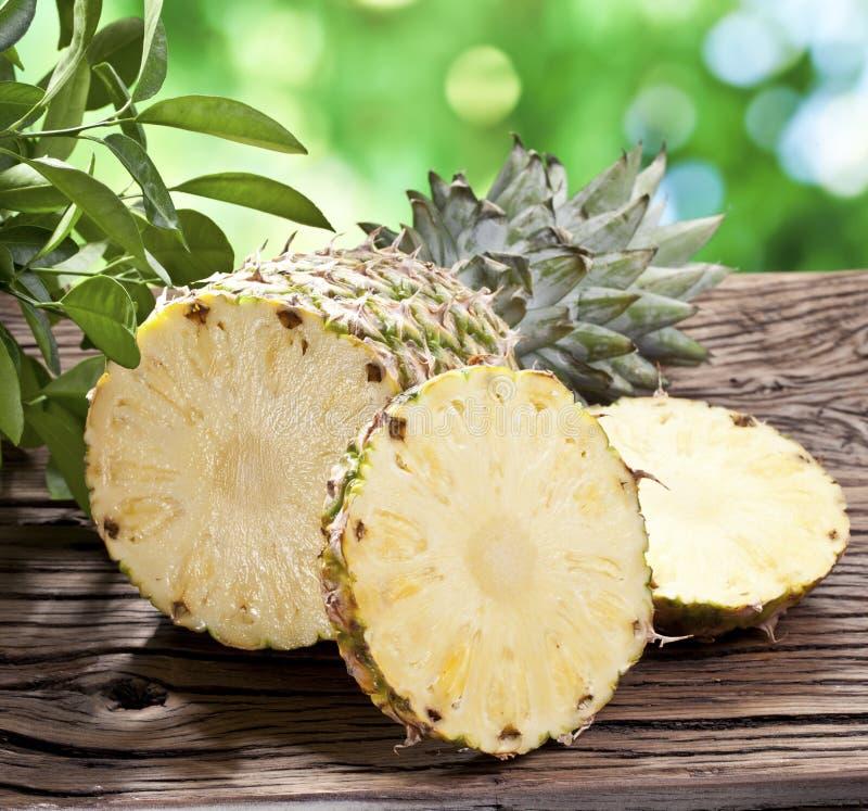 Ananas z plasterkami na drewnianym stole. zdjęcia royalty free