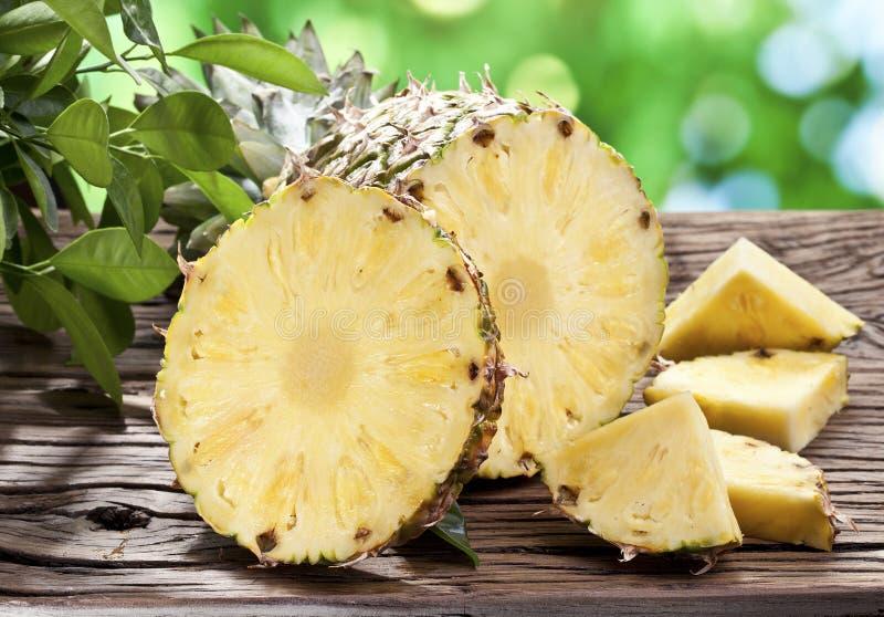 Ananas z plasterkami na drewnianym stole. fotografia stock