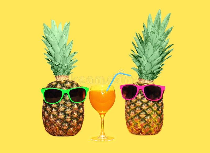 Ananas zwei mit Sonnenbrille und Glasfruchtsaft auf gelbem Hintergrund lizenzfreies stockfoto