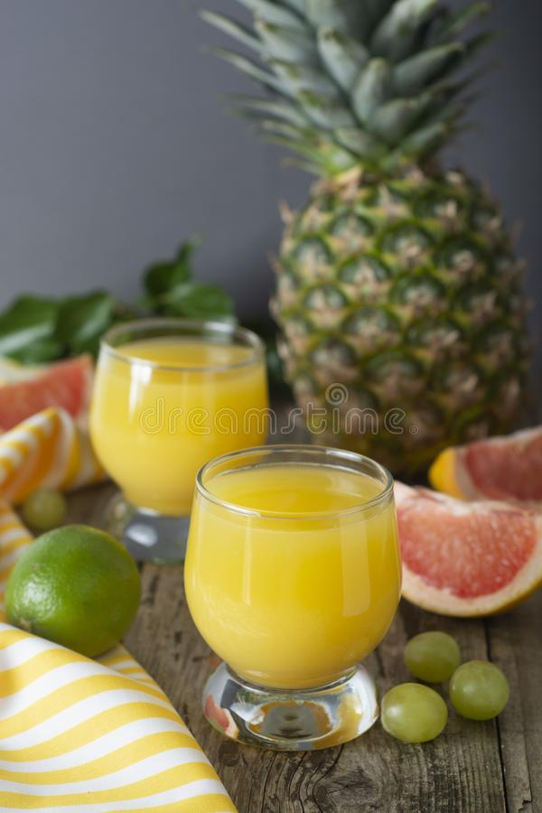 Ananascocktail oder -saft in der Glasgef??flasche mit Strohen und Fr?chten auf Hintergrund - Ananas, Orangen, Pampelmuse, Kalk un stockfotos