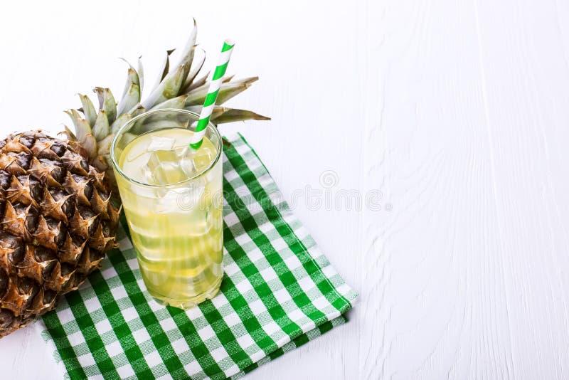 Ananascoctail med is och gr?nt sugr?r, p? en vit tabell Sommarfruktlynne royaltyfria foton
