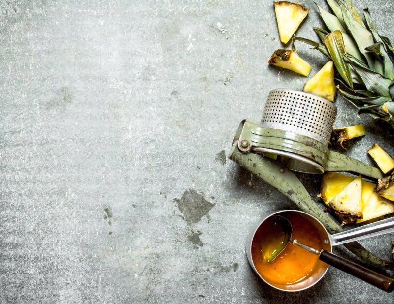 Ananasdriftstopp med en manuell juicer royaltyfri bild