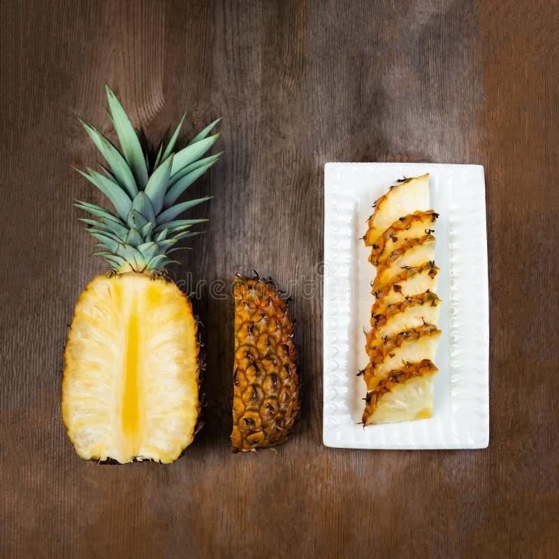 Ananasfrukt klippte halva, fjärdedelen och kilar och visat på den vita plattan och träbakgrund Fyrkantig sammansättning Saftig or royaltyfria bilder