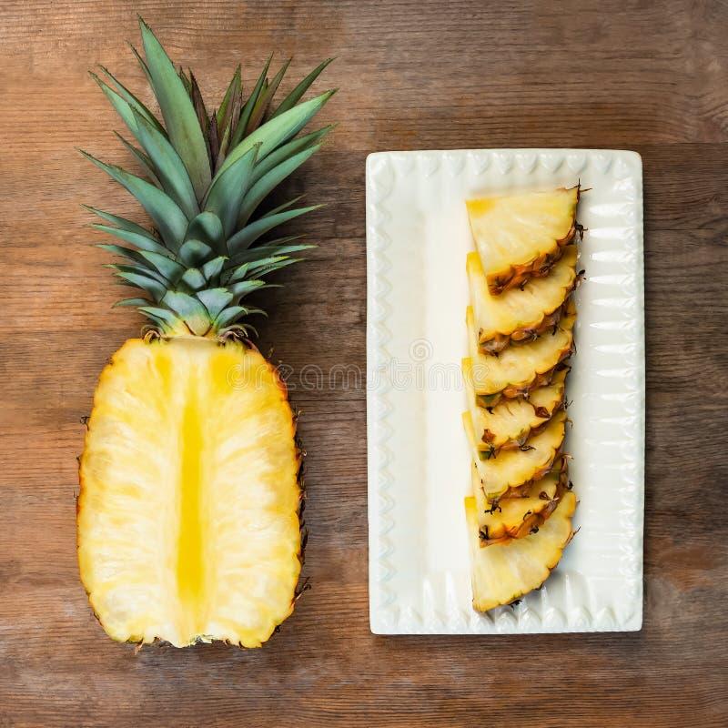 Ananasfrukt klippte halva och kilar och som visade på den vita plattan och träbakgrund Fyrkantig sammansättning Saftig organiskt  royaltyfri bild