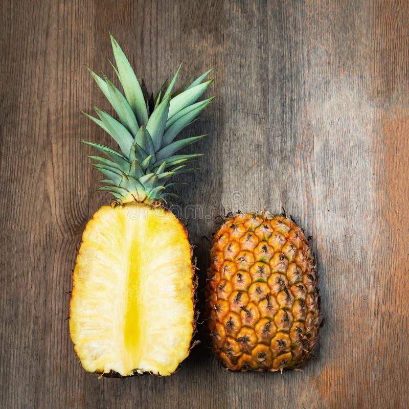 Ananasfrukt klippte två halvor negativt utrymme för bästa träbakgrund arkivbild