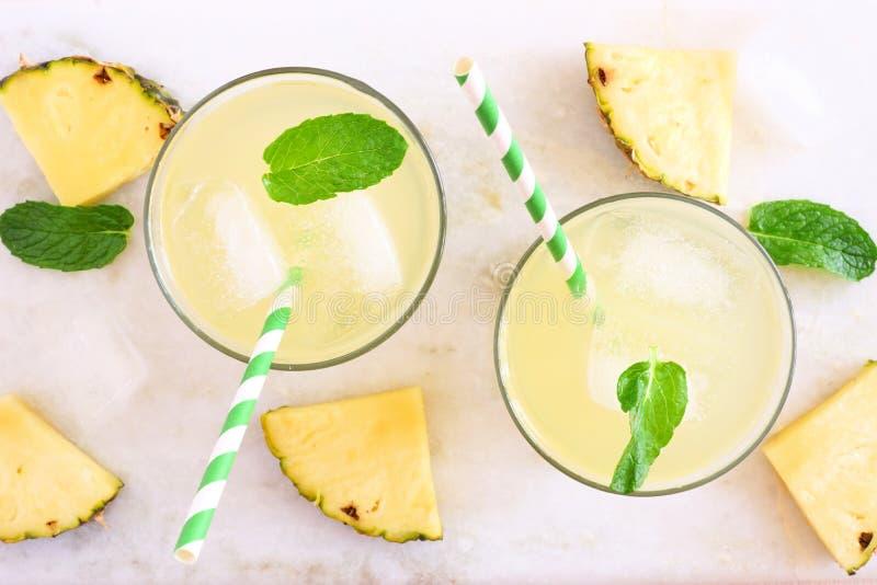 Ananasfruktsaft, bästa sikt på en vit marmorbakgrund arkivfoton
