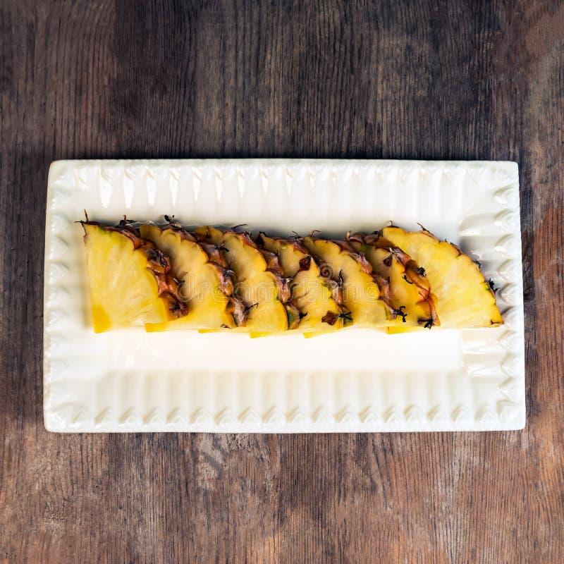 Ananasfruktsnitt i kilar på det sunda mellanmålet plattaför träbakgrund royaltyfri bild