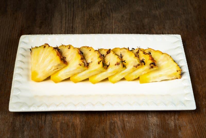 Ananasfruktsnitt i kilar på det sunda mellanmålet plattaför träbakgrund arkivfoto