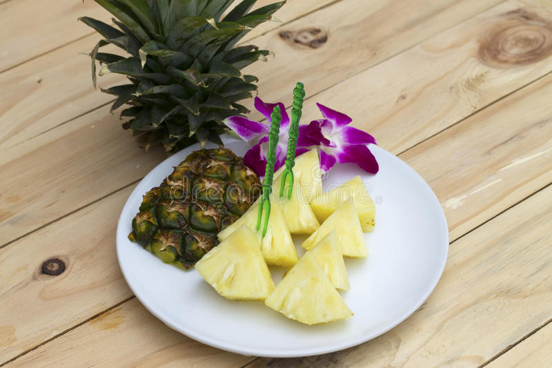 Ananasplakken op de witte schotel op het hout stock afbeelding