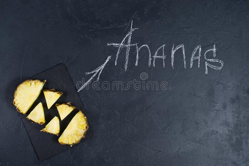 Ananasplakken op zwarte achtergrond met ruimte voor tekst en krijtinschrijving stock afbeelding