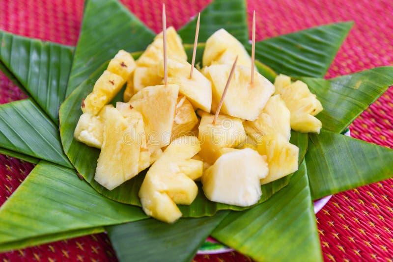 Ananasscheibe auf Bananenblatthintergrund-Fruchtsommer stockfotografie