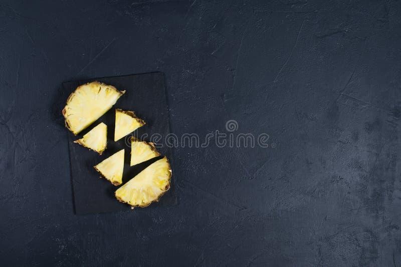 Ananasscheiben auf schwarzem Steinbrett mit Raum f?r Text stock abbildung