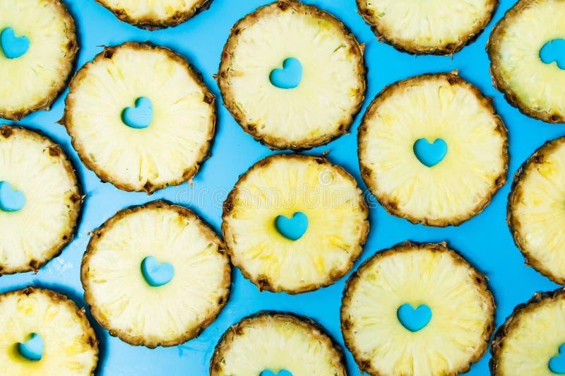 Ananasskivor på blåa den lekmanna- bakgrundslägenheten arkivbilder