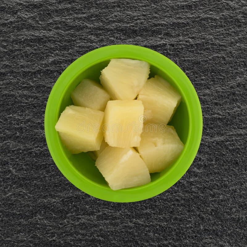 Ananasstora bitar i en bästa sikt för grön bunke arkivbild
