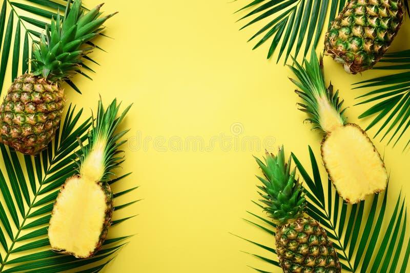 Ananasy i tropikalni palmowi liście na punchy pastelowym żółtym tle pojęcia tła ramy piasek seashells lato Kreatywnie mieszkanie  zdjęcia stock