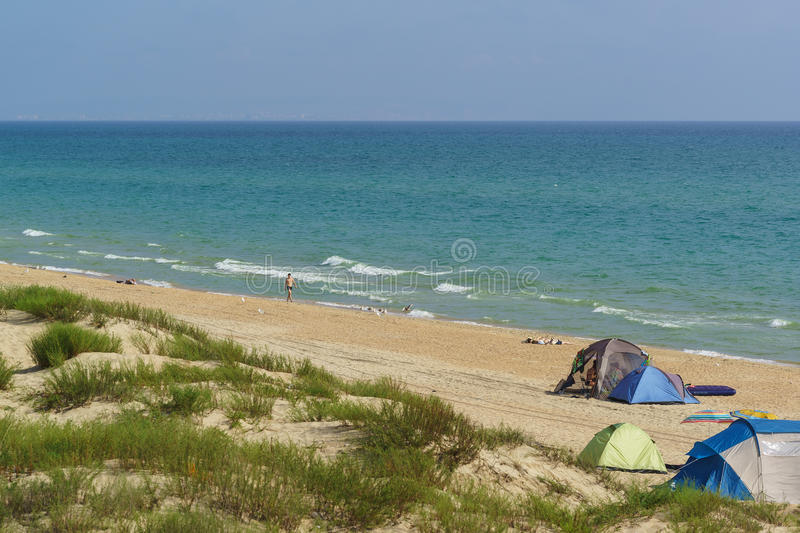 Anapa district Krasnodar Krai Russia - August 15.2015: Tents with vacationers on a wild sandy beach on the Black sea stock image
