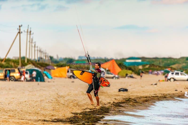 Anapa, Rússia - 9 de julho de 2017: O kitesurfer do homem que guarda a placa de ressaca do papagaio anda fora da água na praia ar fotos de stock
