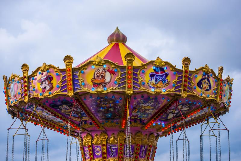 Anapa, Rússia 17 de junho de 2019: O carrossel das crianças em um parque de diversões na iluminação de nivelamento Vintage exteri fotografia de stock royalty free