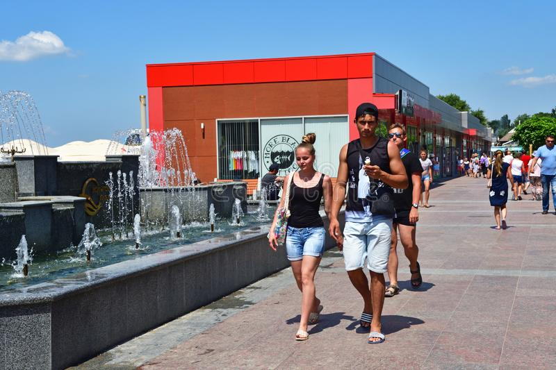 Anapa, Russia, July, 23, 2019. Young man and woman in shorts walking past the fountain on the lower embankment in Anapa. Anapa, Russia. Young man and woman in royalty free stock image