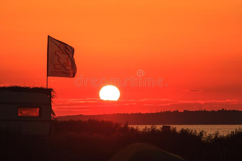 Scenic sunset landscape at Black Sea Blaga Beach resort with waving flag silhouette. Summer seaside scenery with setting sun. Camp stock photography