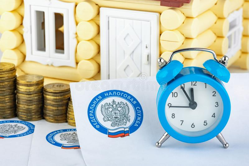 Anapa, Russia - September 3, 2019: Tax notifications, watches, stacks of coins on the background of the house royalty free stock image