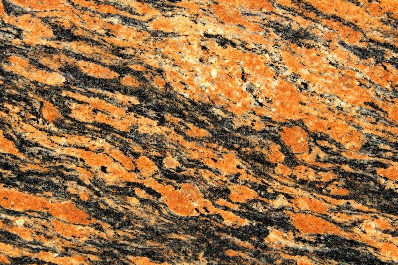 Anaranjado y negro con la textura blanca del granito de los puntos Fondo de piedra natural fotografía de archivo
