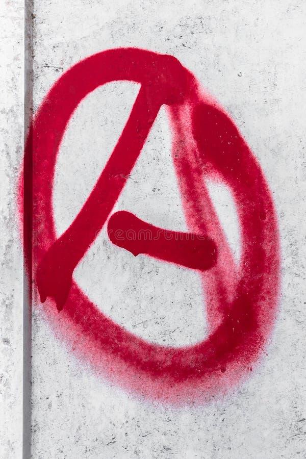 Anarkisymbol som besprutas på den gråa metallbakgrunden arkivfoton