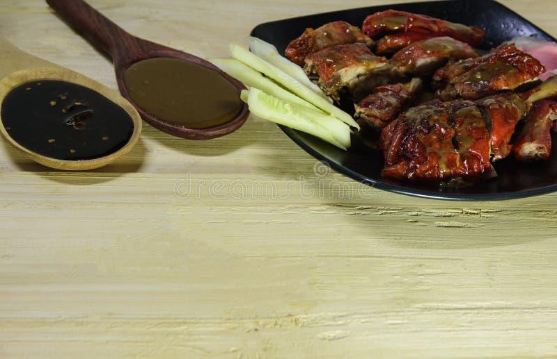 Anatra e verdure di arrosto in banda nera ed in forcella di legno, cucchiaio con salsa su fondo di legno fotografia stock